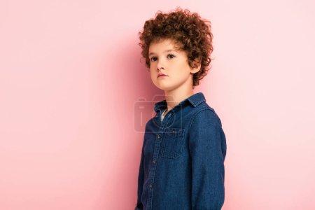 Photo pour Bouclé garçon en denim chemise debout et regardant loin sur rose - image libre de droit