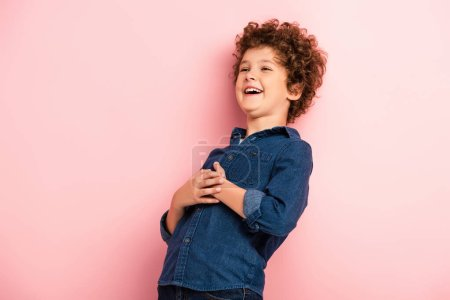 Photo for Joyful and curly boy in denim shirt laughing on pink - Royalty Free Image