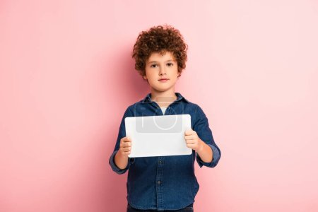 Photo for Curly boy in denim shirt holding digital tablet on pink - Royalty Free Image