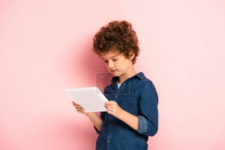 Photo for Curly boy in denim shirt looking at digital tablet on pink - Royalty Free Image