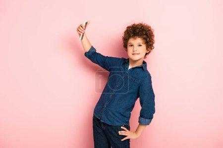 Photo pour Enfant bouclé en chemise denim prendre selfie sur smartphone tout en se tenant avec la main sur la hanche sur rose - image libre de droit
