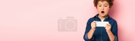Photo for Panoramic concept of surprised boy in denim shirt using smartphone on pink - Royalty Free Image