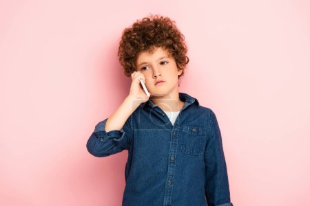 curly boy in denim shirt talking on smartphone on pink