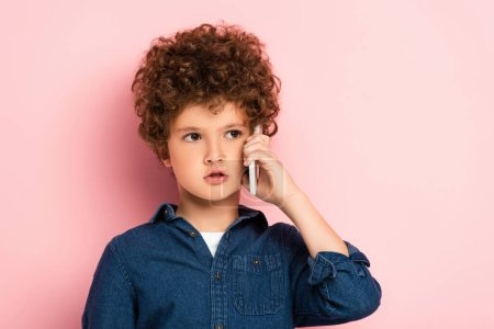 curly boy in denim shirt talking on mobile phone and looking away on pink