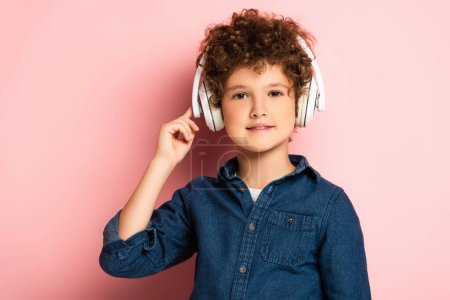 joyful and curly boy listening music and touching wireless headphones on pink