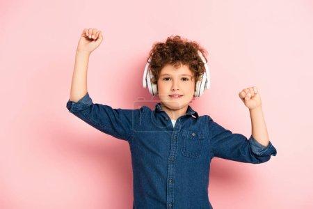 Photo pour Excité et bouclé garçon avec les poings serrés écouter de la musique dans les écouteurs sans fil sur rose - image libre de droit