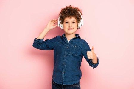 Photo pour Joyeux et bouclé garçon écouter de la musique dans les écouteurs sans fil tout en montrant pouce vers le haut sur rose - image libre de droit