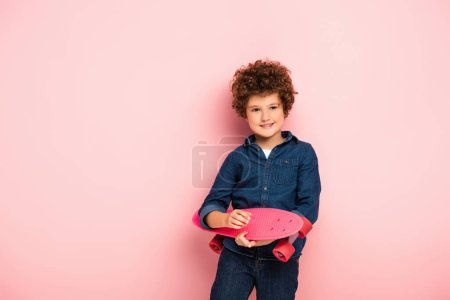 pleased boy holding penny board and smiling on pink