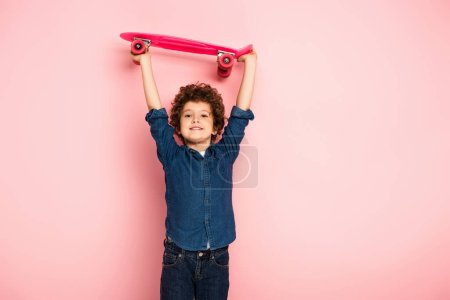 Photo for Curly boy holding penny board above head on pink - Royalty Free Image