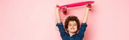 Photo pour Récolte panoramique de garçon bouclé tenant penny conseil au-dessus de la tête sur rose - image libre de droit