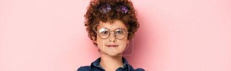 Photo pour Plan panoramique de garçon bouclé en bouquet de lunettes regardant la caméra sur rose - image libre de droit