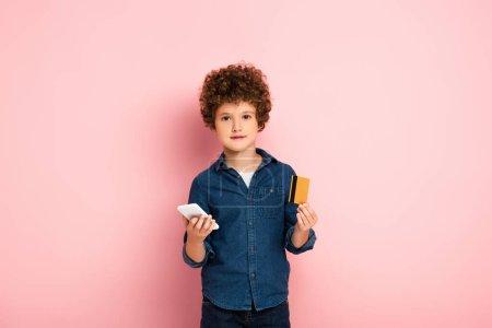 Photo pour Enfant bouclé tenant smartphone et carte de crédit tout en magasinant en ligne sur rose - image libre de droit