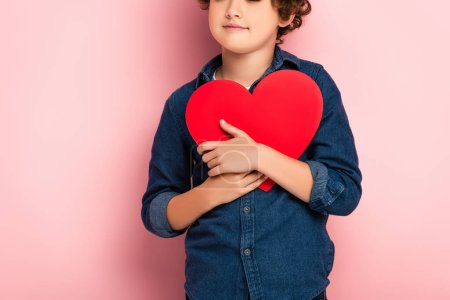 Photo pour Vue recadrée du garçon tenant le papier en forme de coeur coupé sur rose - image libre de droit