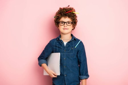 pleased kid in glasses with color pencils in curly hair holding notepad on pink