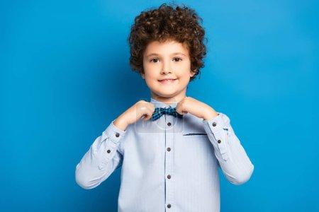 Photo pour Enfant bouclé en chemise touchant noeud papillon et souriant sur bleu - image libre de droit