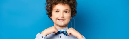 Photo for Horizontal crop of curly kid in shirt touching bow tie and smiling on blue - Royalty Free Image