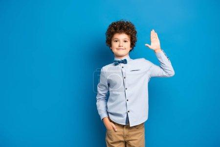 Photo pour Enfant joyeux en chemise et noeud papillon debout avec la main dans la poche et agitant la main sur le bleu - image libre de droit