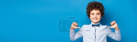 panoramic shot of joyful kid in shirt and bow tie pointing with fingers at himself on blue
