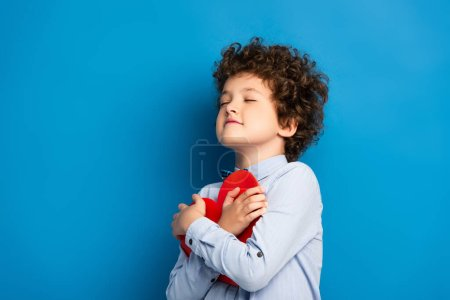 Photo for Joyful kid with closed eyes holding red paper cut heart on blue - Royalty Free Image