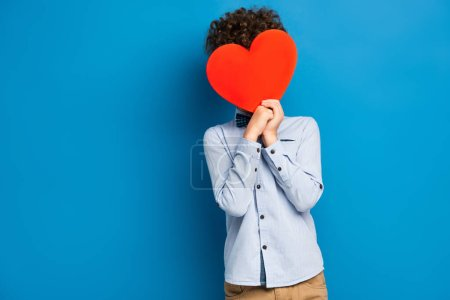 curly boy covering face while holding red paper cut heart on blue