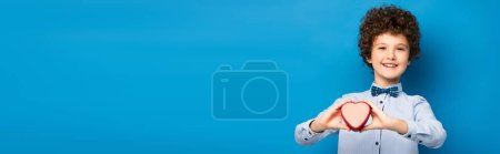 Photo for Panoramic concept of joyful and curly boy holding red heart shape box on blue - Royalty Free Image