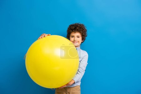 joyful boy in shirt and bow tie holding big yellow balloon on blue