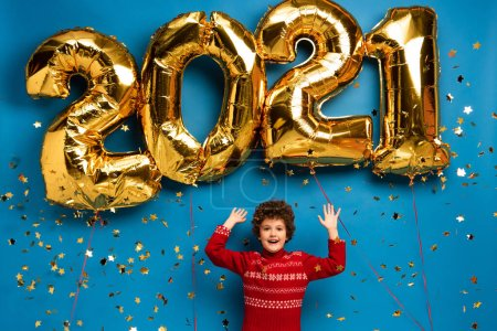 Photo for Excited boy in red sweater gesturing near golden balloons with 2021 numbers and confetti on blue - Royalty Free Image