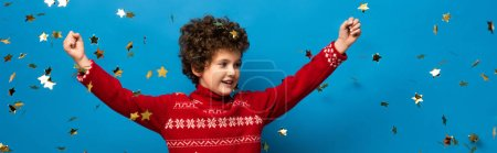 panoramic crop of excited boy with hands above head near golden confetti on blue