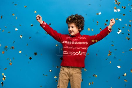 excited boy with hands above head in red sweater near golden confetti on blue