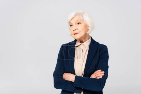 Photo pour Senior woman in jacket standing with crossed arms isolated on grey - image libre de droit
