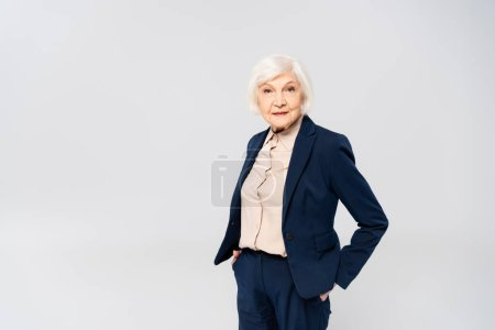 Senior woman looking at camera while standing with hands in pockets of pants isolated on grey