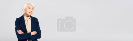 Photo pour Elderly woman with crossed arms looking away isolated on grey, banner - image libre de droit