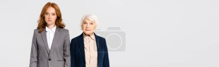 Photo pour Red haired and senior businesswomen looking at camera isolated on grey, banner - image libre de droit