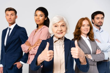 Photo pour Smiling businesswoman showing like near multicultural businesspeople on blurred background isolated on grey - image libre de droit