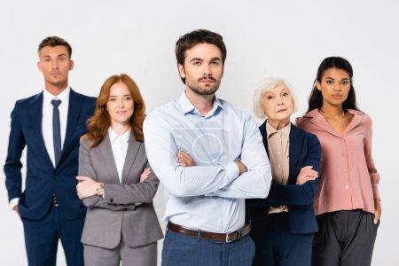Photo pour Homme d'affaires aux bras croisés regardant la caméra près de collègues multiethniques sur fond flou isolé sur gris - image libre de droit