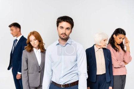 Photo for Businessman looking at camera near sad multiethnic colleagues isolated on grey - Royalty Free Image