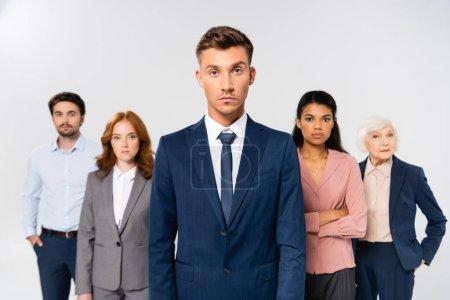 Photo pour Homme d'affaires en costume regardant la caméra près de collègues multiculturels sur fond flou isolé sur gris - image libre de droit