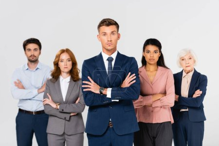 Businessman in formal wear standing with crossed arms near multiethnic colleagues on blurred background isolated on grey