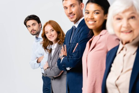 Photo for Smiling businesspeople with crossed arms looking at camera near multiethnic colleagues on blurred foreground isolated on grey - Royalty Free Image