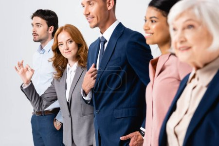 Photo for Businesswoman showing ok gesture near smiling multiethnic colleagues on blurred foreground isolated on grey - Royalty Free Image