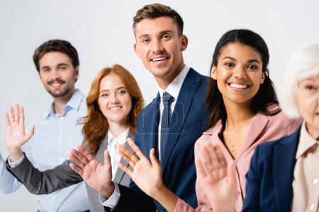 Cheerful businessman waving hand near multicultural colleagues on blurred background isolated on grey
