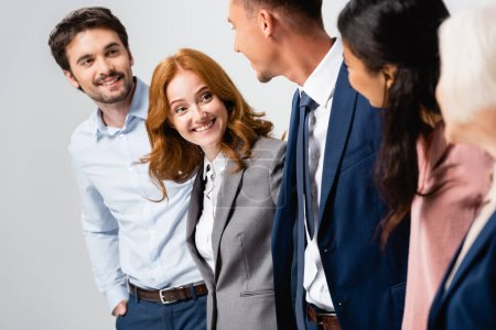 Smiling businesswoman looking at multiethnic colleagues on blurred foreground isolated on grey