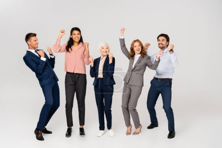 Photo pour Cheerful multiethnic businesspeople showing yes gesture on grey background - image libre de droit
