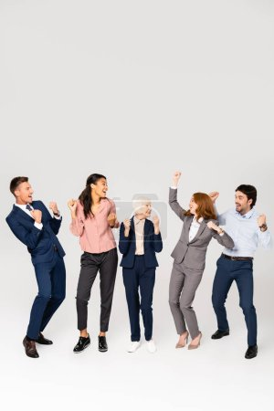 Positive multicultural businesspeople showing yeah gesture on grey background