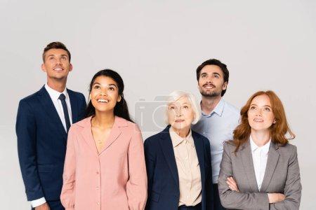Photo pour Des gens d'affaires multiculturels souriants regardant isolés sur le gris - image libre de droit