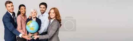 Photo for Smiling multiethnic businesspeople holding globe and looking at camera isolated on grey, banner - Royalty Free Image