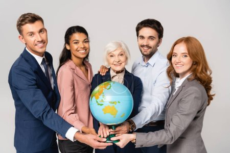 Multicultural businesspeople holding globe while smiling isolated on grey