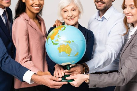 Photo pour Globe in hands of smiling multiethnic businesspeople on blurred background isolated on grey - image libre de droit