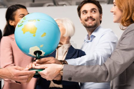 Globe in hands of smiling multiethnic businesspeople on blurred background