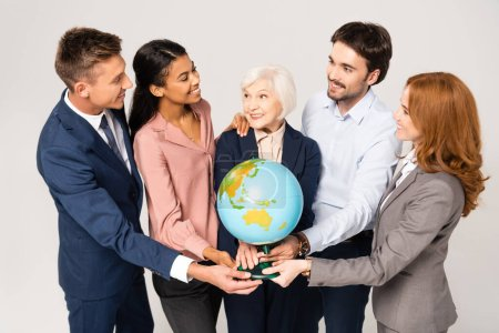 Multicultural businesspeople smiling and embracing while holding globe isolated on grey
